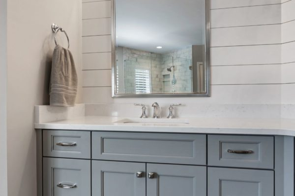 Custom gray vanity cabinet, and shiplap accent wall.