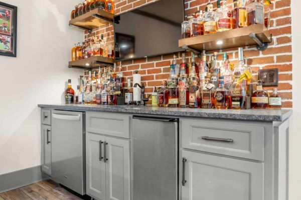 Back bar cabinetry, with built in dishwasher, icemaker, and brick backsplash.