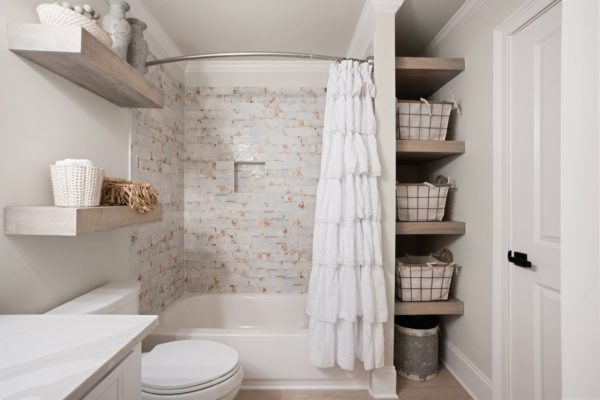 basement bathroom with tile tub surround and floating shelves for storage