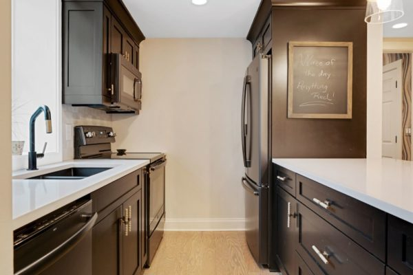 Dark stained custom cabinetry, and white quartz countertops.