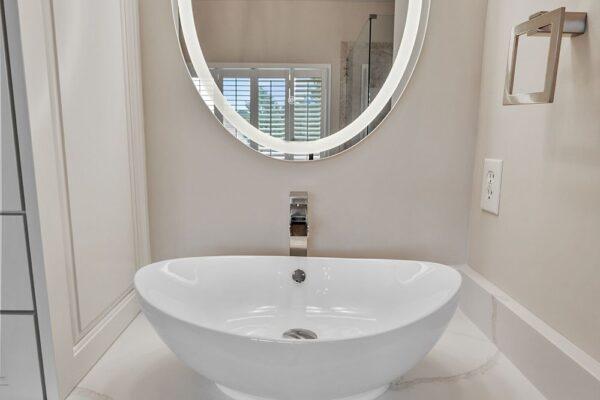 Backlit LED vanity mirror enhance this master bath remodel.
