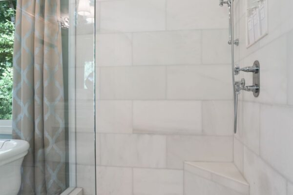 Tile shower with corner bench and mosaic tile floor.