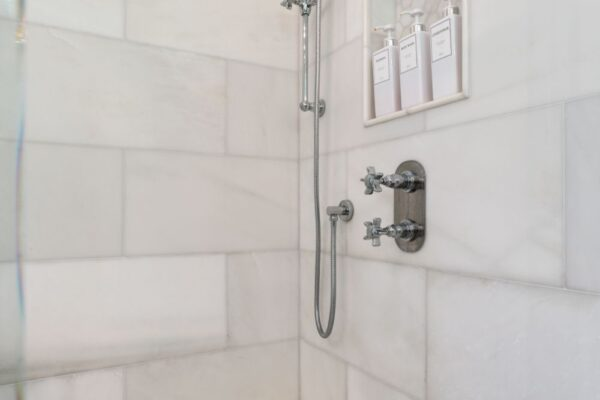 Newly remodeled shower, including a shampoo niche, and seperate handheld faucet.