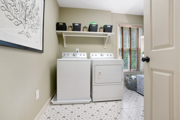 Updated laundry room with new decorative tile flooring.