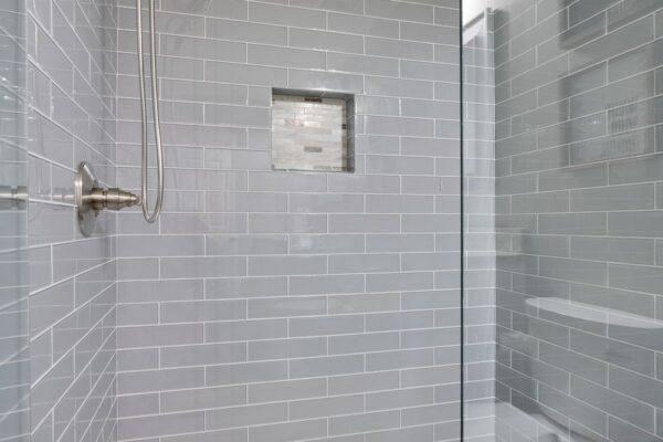 Beautiful tile shower with shampoo niche.