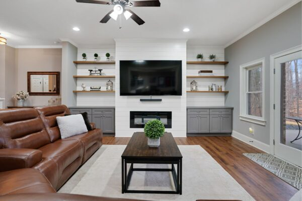 Gray shaker style cabinets, with stained floating shelves.